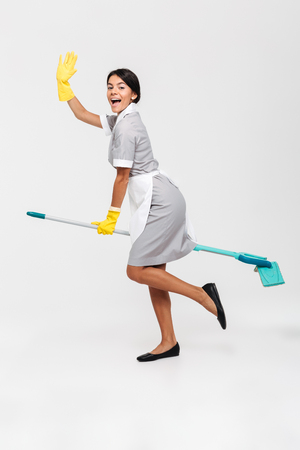 Full length photo of happy funny girl in uniform riding mop as a witch, isolated over white background