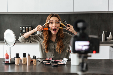 Happy young girl recording her video blog episode about new cosmetic products while sitting at the kitchen table at home and applying make-up Banque d'images