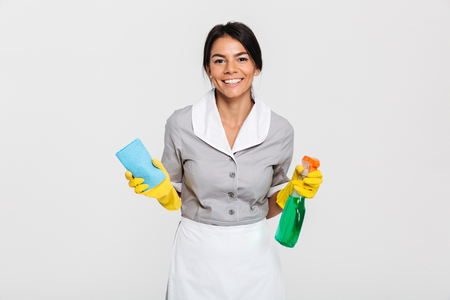 Close-up portrait of cheerful maid in uniform holding rag and cleaning spray, looking at camera, isolated on white background Standard-Bild