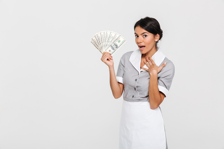 Portrait of amazed young housekeeper in uniform holding fan of dollar banknotes, looking at camera, isolated over white background Stockfoto