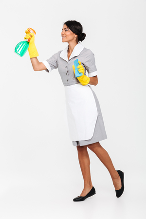 Full length photo of young brunette mais in uniform and yellow protective gloves spraying the cleaner on window, isolated on white background Stock Photo