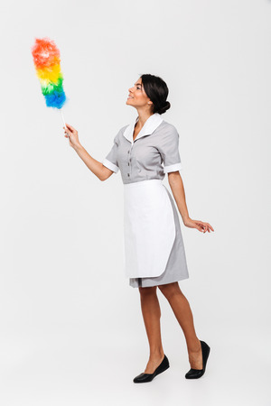 Full length photo of tidy female housekeeper in uniform swipes with dust cleaner, isolated on white background