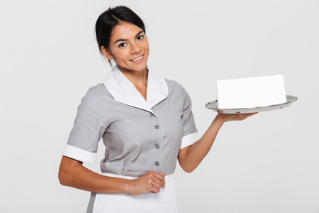 Close-up portrait of beautiful smiling woman in gray uniform holding metal tray with empty sign card, looking at camera, isolated over white background