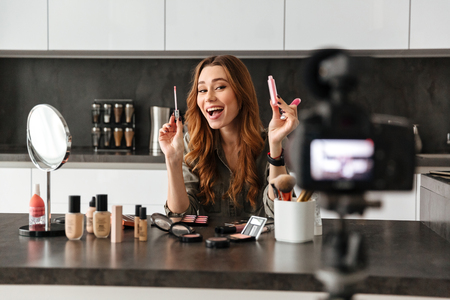 Cheerful healthy young girl recording her video blog episode about new cosmetic products while sitting at the kitchen table at home and applying make-up
