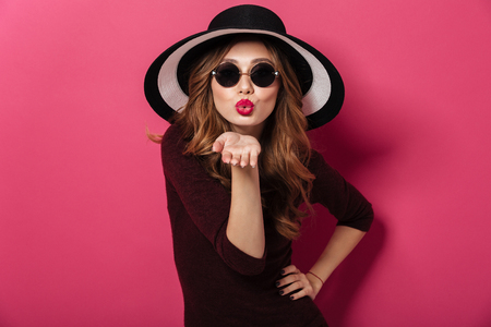 Image of young amazing lady wearing hat and sunglasses standing isolated over pink background. Looking camera blowing kisses.