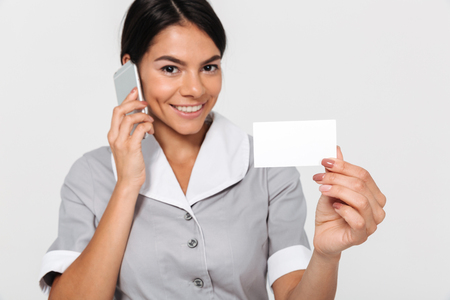 Close-up photo of happy young maid in gray uniform speaking on smartphone while showing empty sign card, isolated on white background Фото со стока