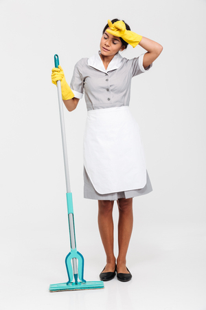 Full length portrait of young tired woman in uniform holding mop and wipes sweat from her forehead, isolated over white background Stock Photo