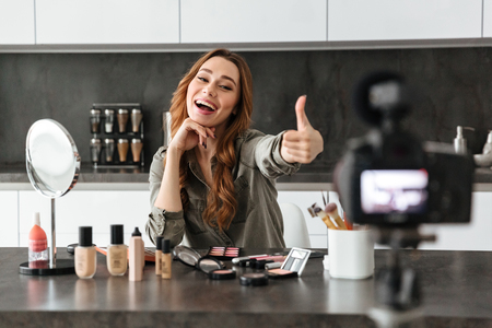 Smiling young girl recording her video blog episode about new cosmetic products while sitting at the kitchen table at home and applying make-up and showing thumbs up gesture Stok Fotoğraf