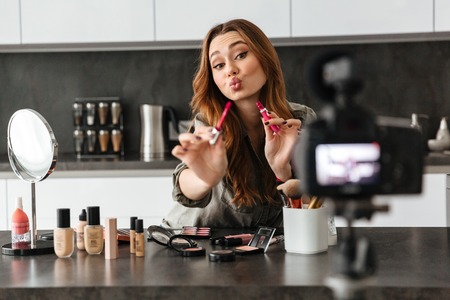 Attractive healthy young girl recording her video blog episode about new cosmetic products while sitting at the kitchen table at home and applying make-up Stock Photo