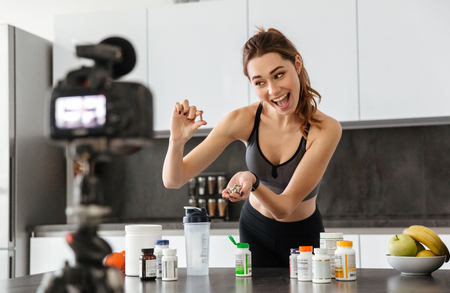 Excited healthy young girl recording her video blog episode about healthy food additives while standing at the kitchen at home Stock Photo