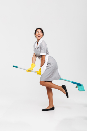 Full length photo of ridiculous young brunette woman in uniform and rubber gloves riding mop as witch, looking aside, isolated over white background