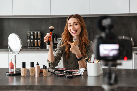 Cheery young girl recording her video blog episode about new cosmetic products while sitting at the kitchen table at home and applying make-up Zdjęcie Seryjne