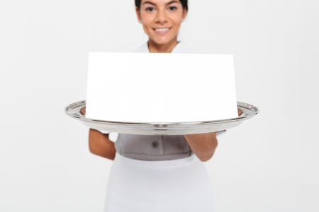 Cropped view photo of young female waiter holding metal tray with empty sign card, selective focus on tray