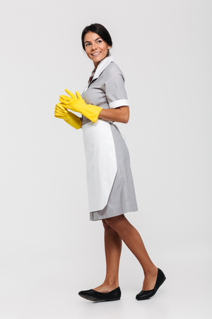 Full length portrait of a happy cheerful housekeeper dressed in uniform posing while standing and looking away isolated over white background