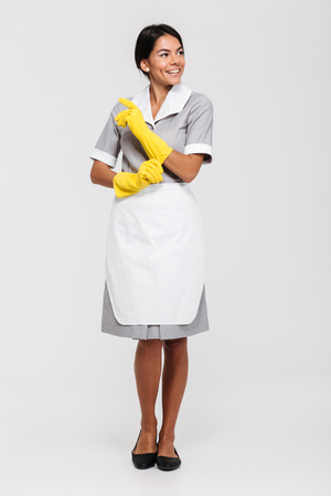 Full length portrait of a attractive smiling housekeeper dressed in uniform posing while standing and looking away isolated over white background Stock fotó