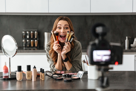 Cheerful young girl recording her video blog episode about new cosmetic products while sitting at the kitchen table at home and applying make-up Stok Fotoğraf