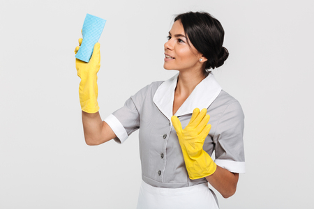 Portrait of a smiling cheery housekeeper dressed in uniform holding a sponge while standing and looking away isolated over white background