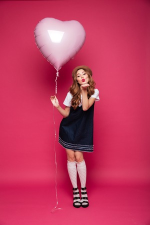 Happy brunette beautiful lady in dress holding air balloon like heart and blowing air kiss isolated over pink Stock Photo