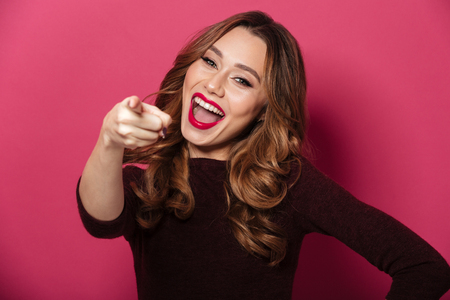 Image of cheerful young beautiful woman standing isolated over pink background. Looking camera pointing.