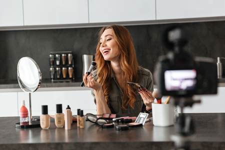 Happy laughing young girl recording her video blog episode about new cosmetic products while sitting at the kitchen table at home and applying make-up