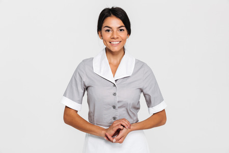 Portrait of pretty smiling maid in uniform keeping hands together and looking at camera, isolated on white background Stok Fotoğraf
