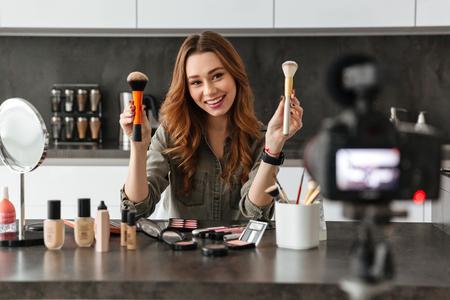 joyeuse jeune fille enregistrant son film vidéo de balayage sur les produits de nouvelle cosmétiques alors qu & # 39 ; il était assis dans la rue de la cuisine à l & # 39 ; extérieur et à l & # 39 ; aide de