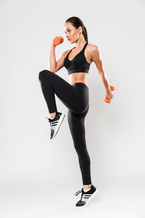 Full length portrait of a healthy young asian fitness woman doing exercises with dumbbells isolated over white background Archivio Fotografico