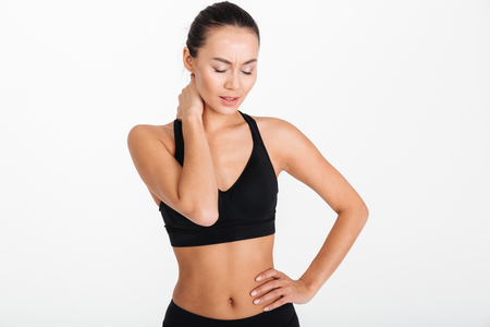 Portrait of a young asian fitness woman suffering from neck pain isolated over white background