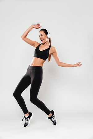 Full length portrait of a happy asian fitness woman wearing headphones posing while standing isolated over white background