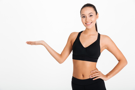 Image of beautiful young sports woman posing isolated over white background. Looking camera holding copyspace. Stock Photo