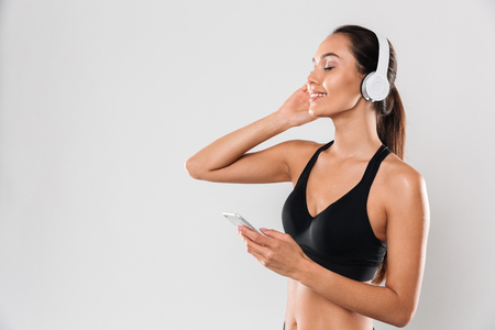 Portrait of a smiling youg asian woman enjoys listening to music with headphones and holding mobile phone isolated over white background