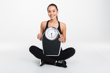 Portrait of a happy asian fitness woman holding weight scales and looking at camera isolated over white background