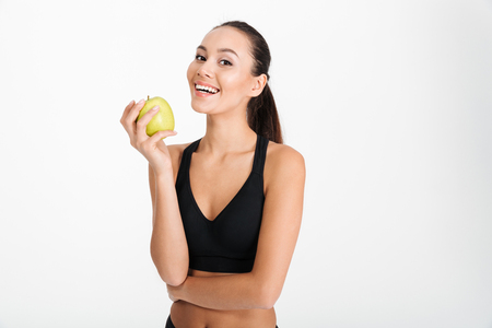 Portrait of a smiling asian fitness woman holding apple isolated over white background