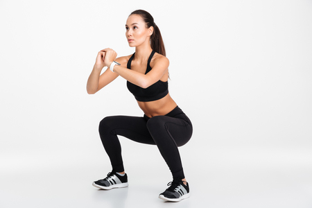 Portrait of a confident asian fitness woman doing squats isolated over white background 스톡 콘텐츠