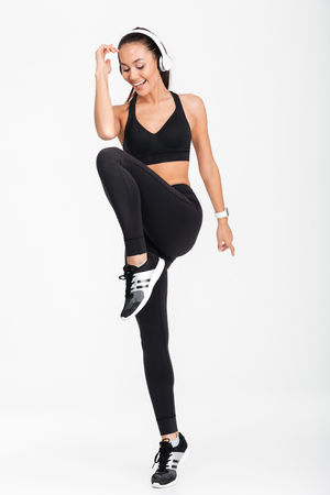 Full length portrait of a smiling asian fitness woman in headphones working out isolated over white background