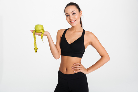 Portrait of a happy asian fitness woman holding apple and measuring tape isolated over white background Foto de archivo