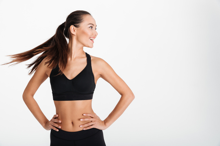 Portrait of a smiling asian fitness girl standing with arms on hips and looking away isolated over white background