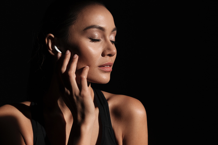 Close up portrait of a beautiful asian woman dressed in sportswear listening to music with mobile phone isolated over black background