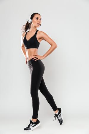 Portrait de toute la longueur d'une femme confiante asiatique fitness portant des écouteurs posant debout et regardant loin isolé sur fond blanc