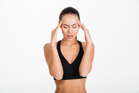 Portrait of a young asian fitness woman suffering from headache isolated over white background