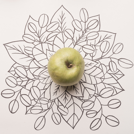 Green apple over outline floral hand drawn background Фото со стока