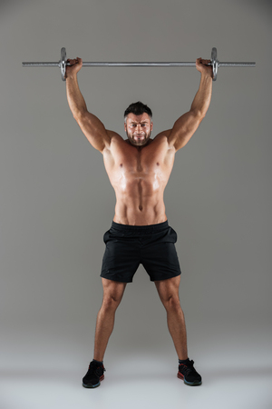 Full length portrait of a muscular serious shirtless male bodybuilder posing with a barbell isolated over gray background Stock Photo
