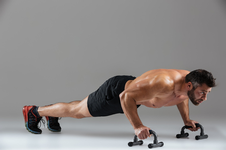 Full length portrait of a muscular strong shirtless male bodybuilder doing push-ups with bars isolated over gray background