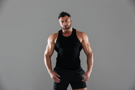 Portrait of a confident serious male bodybuilder standing and looking at camera isolated over gray background