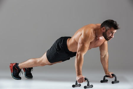 Full length portrait of a fit strong shirtless male bodybuilder doing push-ups with bars isolated over gray background