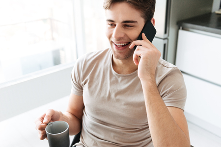 Portrait of cheerful attractive brunette man talking on phone and looking aside in kitchen at home Stock Photo