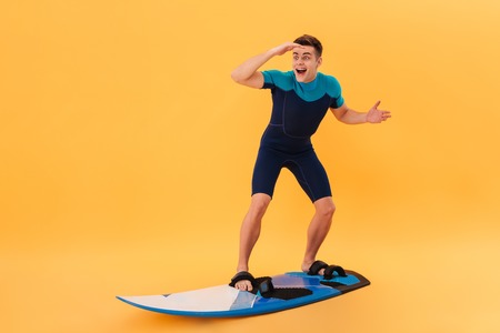 Image of Surprised happy surfer in wetsuit using surfboard like on wave and looking away over yellow background Stock Photo