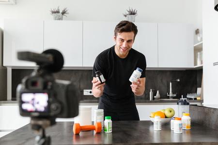 Opgewonden jonge man die zijn video-blog-aflevering over gezonde voedingsadditieven filmt terwijl hij aan de keukentafel staat