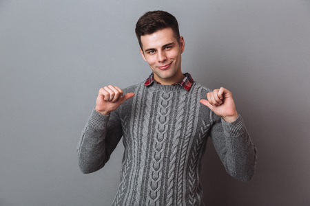 Smiling brunette man in sweater indicates itself and looking at the camera over gray background Stok Fotoğraf