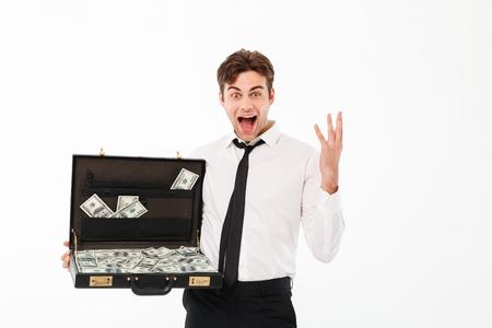 Il ritratto di giovane uomo d'affari allegro si è vestito in camicia bianca che giudica la cartella piena di banconote dei soldi isolate sopra fondo bianco